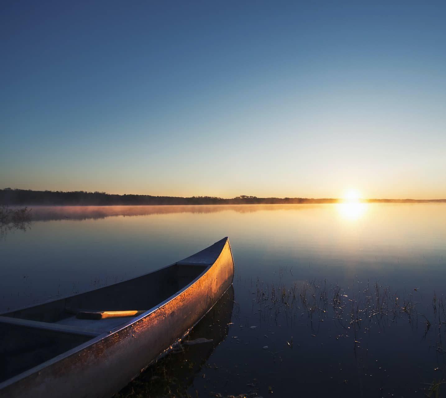 A canoe on a flat calm lake at sunset.